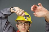 stock photo of overalls  - Cheerful young worker in overalls and a helmet with adjustable wrench in hand - JPG