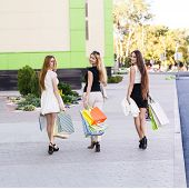 stock photo of girl walking away  - Girls holding shopping bags and walk around the shops - JPG