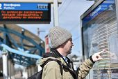 stock photo of passenger train  - Passenger looking at timetable on a Russian commuter train station - JPG