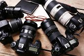 foto of megapixel  - Still life with modern cameras on wooden table - JPG