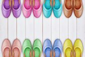 picture of shoes colorful  - a frame of colorful leather shoes on white wooden background - JPG