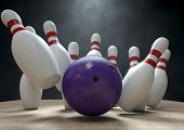 stock photo of bowling ball  - An arrangement of white and red used vintage bowling pins being struck by a bowling ball on a wooden bowling alley surface on a dark background - JPG