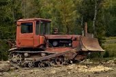 stock photo of bulldozer  - Old rusty bulldozer against the background of green trees - JPG