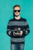 foto of redhead  - Young redhead man in a sweater and jeans and sunglasses standing next to turquoise wall and taking photos vintage camera warm summer sunny day - JPG