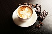 picture of latte  - Cup of latte art coffee with grains and bar of chocolate on wooden background - JPG