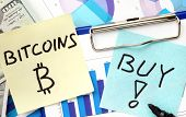 picture of bitcoin  - Paper with words bitcoins and buy and graphs - JPG