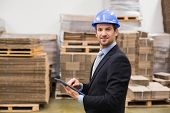 stock photo of warehouse  - Warehouse manager wearing hard hat using tablet in a large warehouse - JPG
