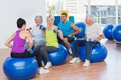 foto of senior class  - Female instructor with class lifting dumbbells in gym class - JPG