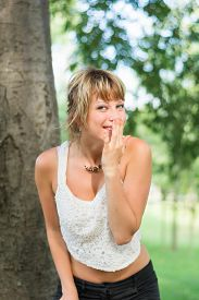 stock photo of cheeky  - Blonde young woman outdoors laughing and hiding mouth with her hand - JPG