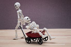 stock photo of wagon  - Two skeletons playing with a red toy wagon - JPG