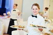 waitress occupation. Young woman with food on dishes servicing in restaurant during catering the eve poster