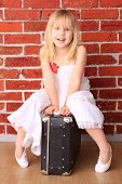 Beautiful Little Girl Sitting On A Suitcase And Laughs