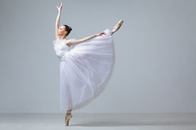 stock photo of ballet dancer  - cute young and beautiful ballet dancer jumping - JPG