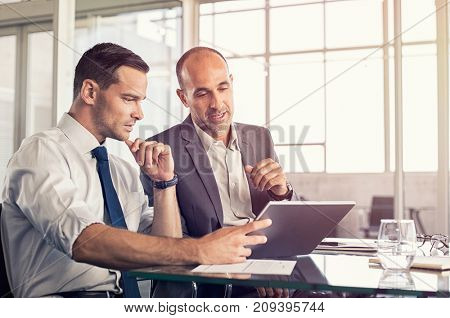 poster of Businessman using a digital tablet to discuss information with senior leadership in a meeting. Busin