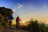 Cycling women and man riding on bikes at sunset mountains forest landscape. Couple cycling MTB endur poster