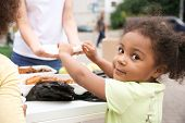 Volunteer sharing food with poor African child outdoors poster
