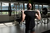 Athlete In The Gym Exercising Shoulder With Barbell poster