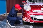 Man cleaning automobile with sponge at car wash poster
