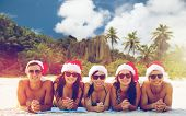 christmas, travel, winter holidays and people concept - group of friends in santa helper hats sittin poster