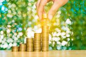 Woman Hand Put Coin On Step Of Coins Stacks And Gold Coin Money In The Glass Jar On Table In Garden poster