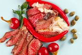 grilled meat portion on blue plate over white