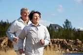 Portrait of happy mature couple running together