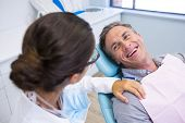 Happy patient sitting on chair while looking at dentist in medical clinic poster
