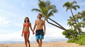 Couple walking on beach. Young happy interracial couple walking on beach smiling holding hands in sw poster