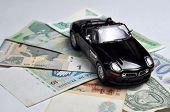 Black sport car and money on white