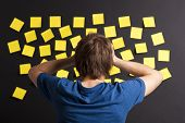 foto of post-teen  - Young student with stress and looking to a board full of yellow notes - JPG