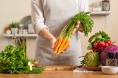Chef Is Holding A Fresh Carrot. The Concept Of Losing Healthy And Wholesome Food, Detox, Vegan Eatin poster