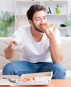 Man eating pizza having a takeaway at home relaxing resting poster