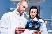 Dentista e Assistente de verificação de raios-x na clínica odontológica