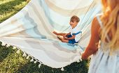 Image Of Little Brother And His Sister Playing With The Blanket On Green Grass. Happy Little Boy And poster