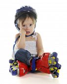 An adorable preschooler weepy because her plastic roller blades made her fall.  On a white background.