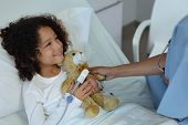 Side view of mixed race female doctor giving teddy bear to child patient in the ward at hospital poster