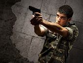 picture of glock  - portrait of a young soldier aiming with a pistol against a grunge brick wall - JPG