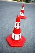 An image of caution cone sign on asphalt road.