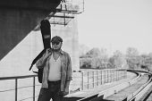 Bluesman With Guitar Case Walks On Railroad. Blues Musician On Railway In Grayscale. Cool Guy With G poster