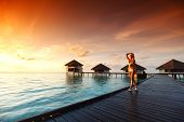 woman in a dress on a bridge home sea and the maldivian sunset on the background