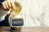A Man Puts Dollars In A Glass Jar With The Word Profit. Concept Of Business Success, Financial Growt poster