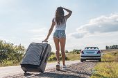 Back View Young Asian Woman Traveller In Sexy Denim Shorts Holding Luggage And Waiting Car On Roadsi poster