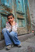 Um menino sentado à porta de casa