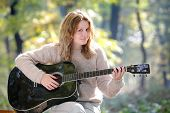 stock photo of acoustic guitar  - Young Caucasian girl in forest with guitar selective focus - JPG