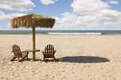 Two Beach Chairs and Umbrella on a Beautiful Ocean Front with Copy Space.