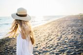 Young Attractive Long Haired Blonde Girl In Straw Hat Relaxing At The Beach At Sunset. Soft Sunset L poster