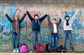 Happy teenage boys and girls having fun in urban environment after the school