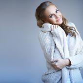 Beautiful woman in winter fashion snuggling up in the warmth of her stylish knitted wool jersey with a smile of pleasure