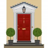 stock photo of planters  - Traditional red-painted front door with lantern, brass bell-pull, letterbox and door-knocker. Clipped  topiary bay trees in decorative planters standing on the entrance steps.