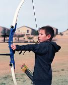 pic of fletching  - Close up of a young boy drawing back a bow and arrow - JPG